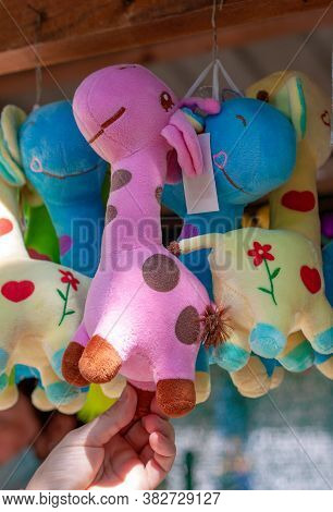 Multi-colored Soft Toy Giraffe Hang  The Souvenir Counter.  The Pink One Is In The Center.  The Sun