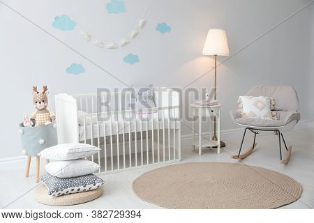 Stylish Baby Room Interior With Crib And Rocking Chair
