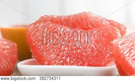 Delicious Pink Grapefruit Ready For Eating And Brushed On A Wooden Table, Close-up