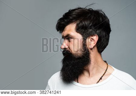Half-turned Side Profile Portrait Of Serious Man Has Beard And Mustache, Looks Seriously, Isolated O