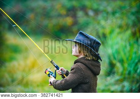 Kid With Fishing Rod At Lake. Little Boy Catching A Fish. Lonely Happy Little Child Fishing From Bea