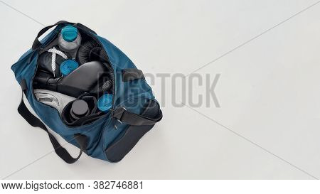 Boxing Gear And Accessories. Top View Of Sports Bag With Boxing Gloves, Hand Wraps, Clothing, Bottle