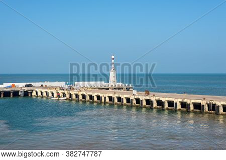 Mormugao, Goa, India - November 23, 2019: View On The Mormugao Breakwater Lighthouse And Pier In Sou