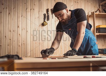 Experienced Carpenter In Work Clothes And Small Business Owner Working In Woodwork Workshop,  Using