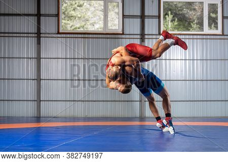Two Men In Sports Wrestling Tights And Wrestling During A Traditional Greco-roman Wrestling In Fight
