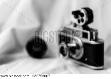 Blurred Photo Of A Retro Camera With An External Drum Range Finder. Space For Lettering Or Design.