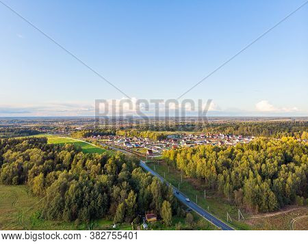Bright Summer Suburban Landscape Shot From A Birds Eye View. Horizon Line, Blue Sky With Clouds.