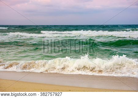 Dramatic Weather On The Seashore. Green Waves Crashing On The Beach. Cloudy Purple Sky In Evening Li