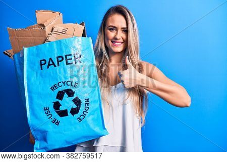 Young beautiful blonde woman recycling holding paper recycle bag full of paperboard smiling happy and positive, thumb up doing excellent and approval sign
