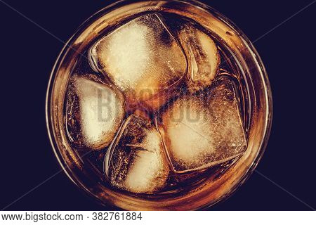 A Glass Of Cola With Ice Close-up In The Dark. Brown Carbonated Drink, Non-alcoholic Beverage With C