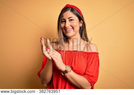 Young beautiful woman colorful summer style over yellow isolated background clapping and applauding happy and joyful, smiling proud hands together