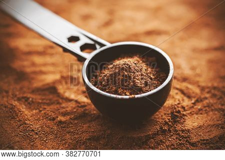 Against The Background Of Ground Coffee Lies A Long Black Measuring Spoon, Which Is Also Filled With