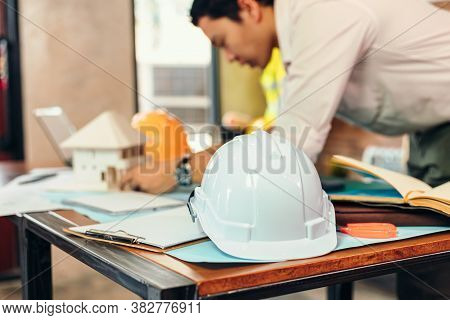 Safety Helmets  On The Table At Site Construction. Architect, Engineer And Businessman  Read  Planni