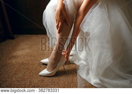 The Bride In A Beautiful Wedding Dress Puts On Shoes, The Morning Of The Bride, A Beautiful Girl Wai