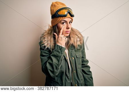 Young brunette skier woman wearing snow clothes and ski goggles over white background Pointing to the eye watching you gesture, suspicious expression