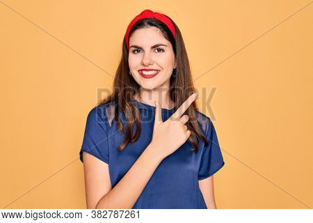Young beautiful brunette woman wearing red lips over yellow background cheerful with a smile of face pointing with hand and finger up to the side with happy and natural expression on face