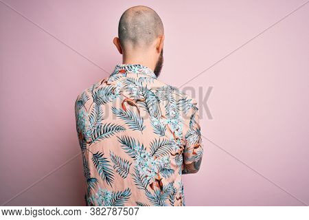 Handsome bald man with beard and tattoo wearing casual floral shirt over pink background standing backwards looking away with crossed arms