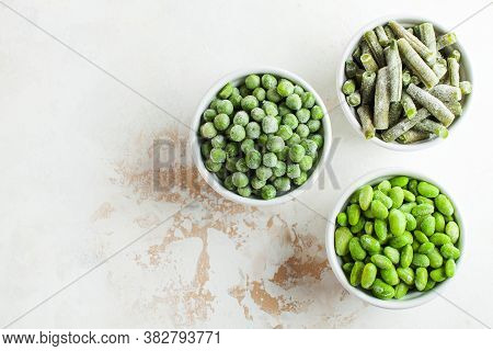 Frozen Vegetables Green Peas, Soy, Green Beans, And Baby Food In White Bowls With Copy Space. Health