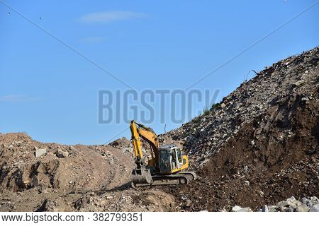 Yellow Excavator At Landfill For Disposal Of Construction Waste. Backhoe Dig Gravel At Mining Quarry