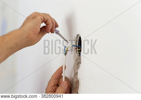 Closeup View Of Electrician Checking The Presence Of Electrical Current In A Wire Circuit In A Home.
