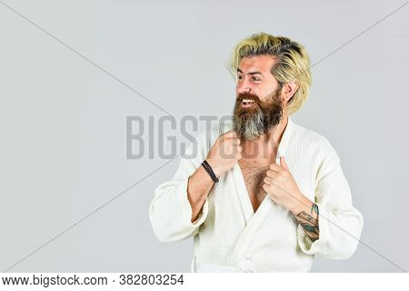Man In Bathrobe In Bathroom. Hygiene And Spa. Spa Resort. Hotel Apartments. Bearded Guy Wearing Whit