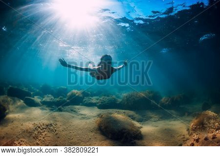 Attractive Woman Dive Near Stone With Seaweed In Underwater. Swimming In Ocean