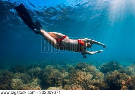 Slim Woman In Bikini Glides At Blue Sea With Sun Rays. Freediving With Fins Underwater In Sea