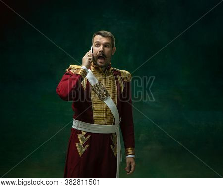 Phone Talking. Young Man In Suit As Nicholas Ii On Dark Green Background. Retro Style, Comparison Of
