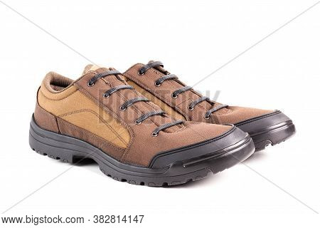 A Pair Of Cheap Brown Fabric Hiking Or Hunting Shoes With Elastic Rubber Laces Isolated On White Bac