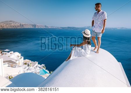 Couple Men And Woman On Vacation Santorini, View To The Sea And Volcano From Fira The Capital Of San