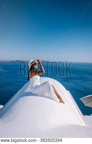 Santorini Greece, Young Woman On Luxury Vacation At The Island Of Santorini Watching Sunrise By The