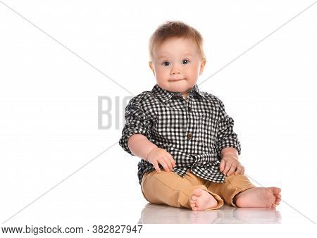 Portrait Of Infant Child Baby Boy Toddler With Dark Blue Eyes Dressed In Beige Pants And A Checkered