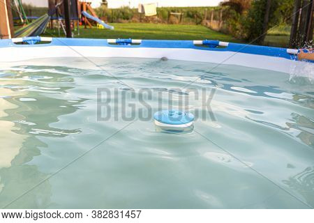 Blue Chlorine Dispenser Floating In A Home Pool In Garden, Cleaning And Care Of The Domestic Pool.