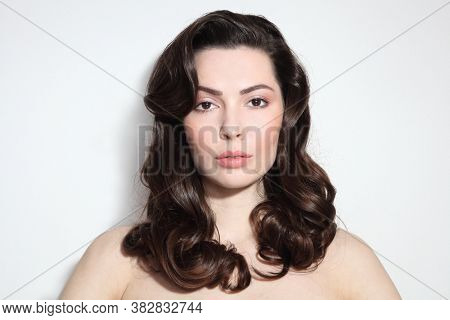 Young beautiful brunette with long curly hair and makeup