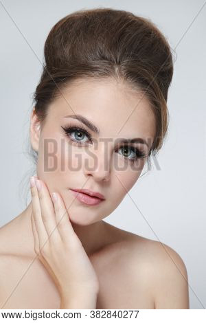 Vintage style portrait of young beautiful woman with fancy hair bun and natural makeup