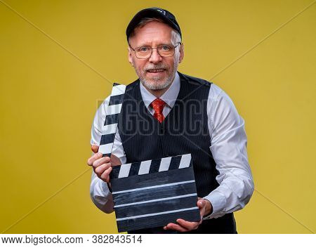 Senior Man Holds Film Flap Close Up. Film Directing. Film Production. Human Emotions. Man With Movie