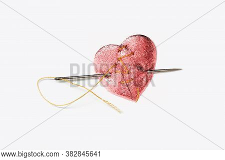 Broken Heart Stitched Thread On A White Background. Needle Is Stuck In The Heart