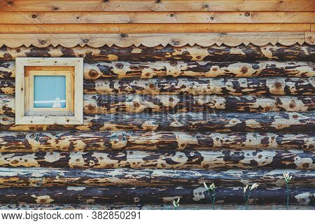 Frontal View Of A Bath Blockhouse Facade Made Of Roughly Hewn Yellowish Tree Trunks, With A Single W