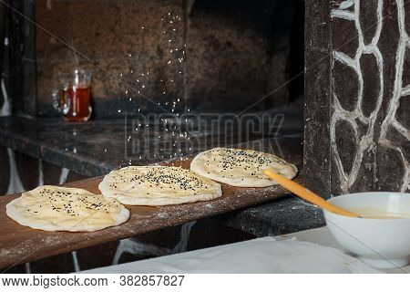 Before Baking In The Oven, The Chef Sprinkles The Buns With Sesame Seeds. Buns For Making Traditiona