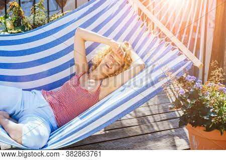 Young Blond Woman Relaxed Lies In Strip Hammock On Balcony At House. Mature Romantic Female In Strip