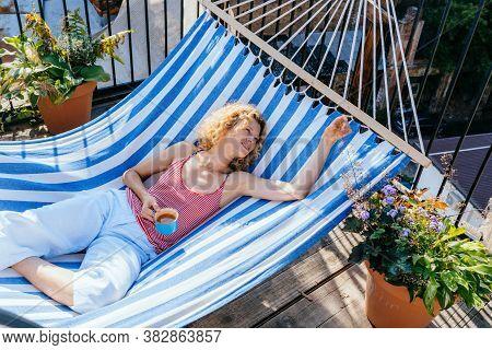 Blond Romantic Caucasian Woman Drinks Tea, Smiling Happy Resting In Comfortable Hammock At Home. Mat