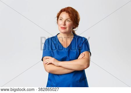 Thoughtful Redhead Nurse, Physician Or Female Doctor In Scrubs Looking Upper Left Corner With Intrig