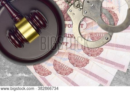500 Hungarian Forint Bills And Judge Hammer With Police Handcuffs On Court Desk. Concept Of Judicial