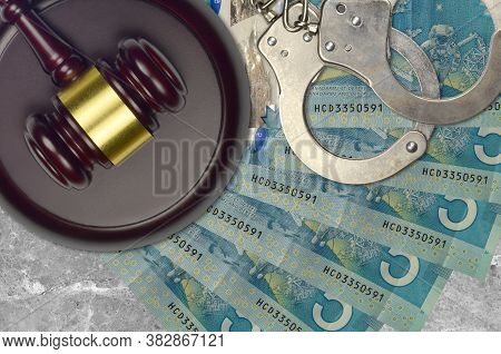 5 Canadian Dollars Bills And Judge Hammer With Police Handcuffs On Court Desk. Concept Of Judicial T