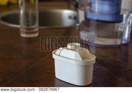 Close-up Of A Tap Water Purification Cartridge. White Plastic Cartridge On The Kitchen Table. Health