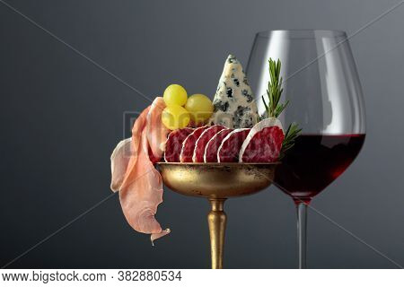 Wine, Blue Cheese, Dry-cured Sausage, Grapes, And Rosemary On A Black Background. Simple And Tasty F