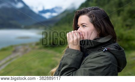 A Woman Warms Her Hands With Warm Breath On A Cold Morning. Woman Tourist Blows On Her Hands Warming
