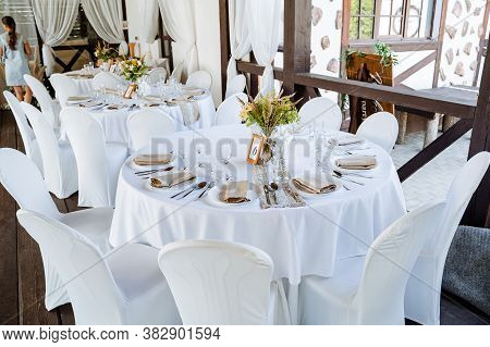 Serving A Festive Table, Placing Plates On The Table, A Banquet Table With A White Tablecloth, Prepa