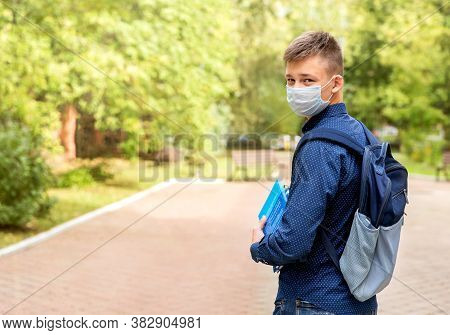 A Teenager In A Medical Mask With Books In His Hands In The Schoolyard. He Turned Around. He Has Sch
