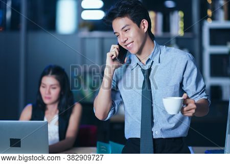 Businesspeople In The Office At Night Working Late, Coffee And  Calling Phone Working Overtime Toget